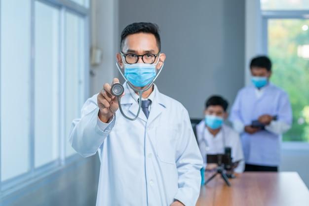 Cuidados de saúde asiáticos e conceito médico. médico de medicina usar máscara médica com estetoscópio na mão e equipe de pesquisa no hospital novo fundo normal da bandeira.