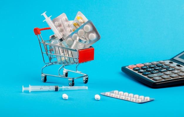 Cuidados de saúde caros. carrinho de compras com remédios e calculadora