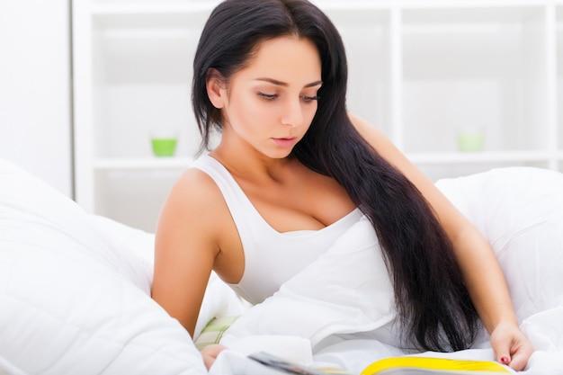 Cuidados de saúde. closeup de linda mulher doente com dor de cabeça, dor de garganta e febre, coberto de cobertor, sentindo-se doente, medindo a temperatura corporal com termômetro. doença e doença.