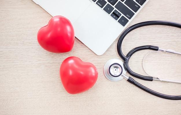 Cuidados de saúde de lareira com estetoscópio e computador na mesa do médico,