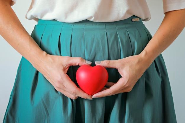 Cuidados de saúde de mulher, gravidez e ginecologia conceito. as mãos de uma mulher segurando um símbolo do coração na barriga