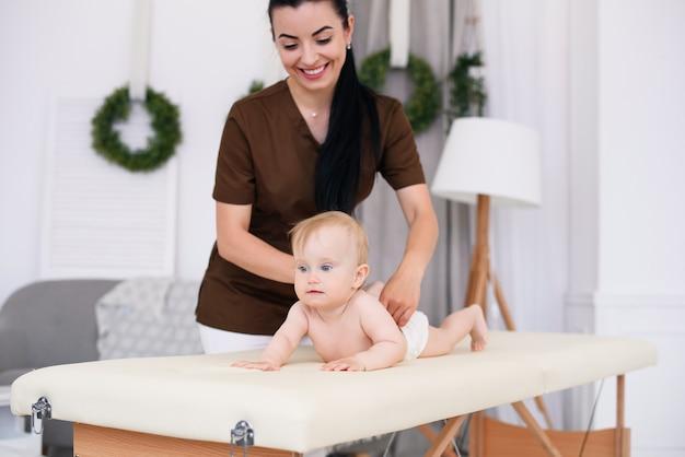 Cuidados de saúde e conceito médico. bebê feliz tendo massagem com massagista profissional feminina. médico infantil gentil e amigável. massagem infantil no sofá em um quarto moderno e aconchegante.