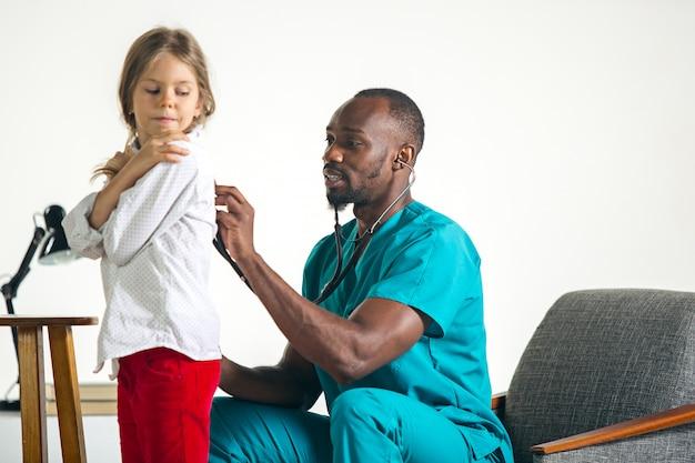 Cuidados de saúde e conceito médico - médico com estetoscópio, ouvindo o peito de criança no hospital