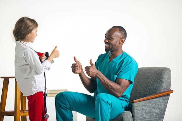 Cuidados de saúde e conceito médico - médico e menina com estetoscópio no hospital