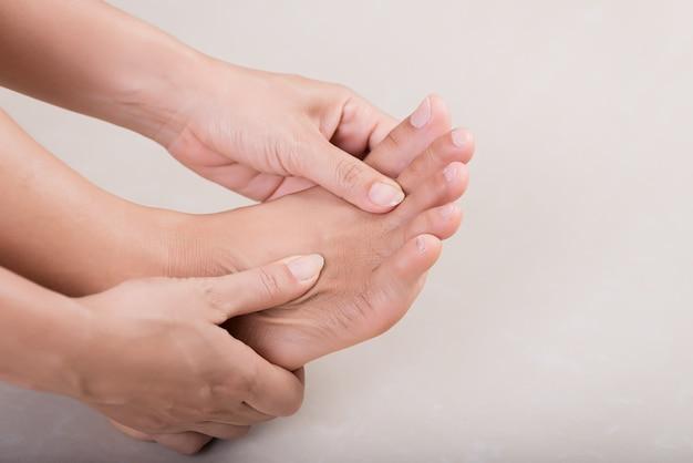 Cuidados de saúde e médicos. mulher massageando seu pé doloroso.