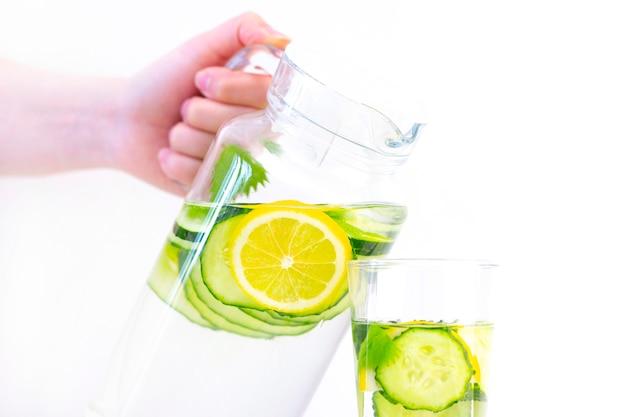 Cuidados de saúde, fitness, conceito de alimentação saudável. bebida fresca de pepino limão fresco com água, coquetel, bebida desintoxicante, limonada em uma jarra de vidro e um copo.