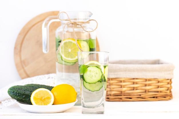 Cuidados de saúde, fitness, conceito de alimentação saudável. pepino com limão fresco e fresco com água, coquetel, bebida desintoxicante, limonada em uma jarra de vidro e um copo. pepinos e limão em um prato
