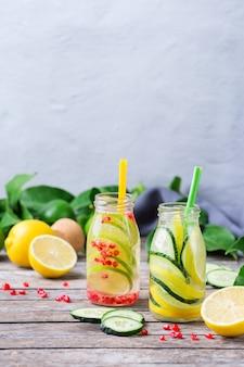 Cuidados de saúde, fitness, conceito de dieta de nutrição saudável. fresco fresco limão pepino alecrim romã infundido água, bebida desintoxicante, limonada em uma jarra de vidro para dias de primavera verão. copie o fundo do espaço