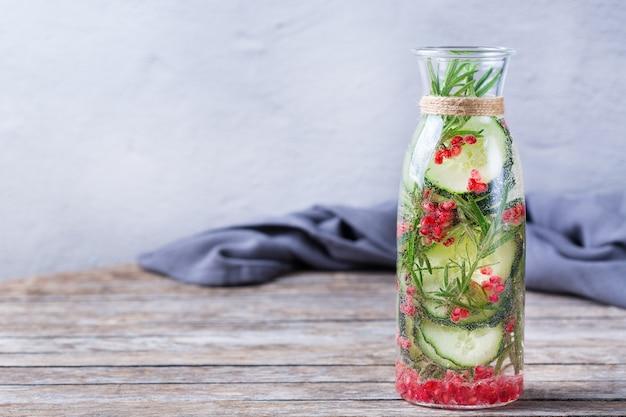 Cuidados de saúde, fitness, conceito de dieta de nutrição saudável. fresco fresco pepino romã alecrim infundido água, bebida desintoxicação, limonada em uma jarra de vidro para dias de primavera verão. copie o fundo do espaço
