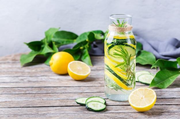 Cuidados de saúde, fitness, conceito de dieta de nutrição saudável. limão fresco, pepino, alecrim, água infundida, bebida desintoxicante, limonada em uma jarra de vidro para os dias de primavera e verão. copie o fundo do espaço