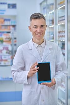 Cuidados de saúde. homem adulto alegre de jaleco branco mostrando a tela do tablet em pé perto de prateleiras com remédios na farmácia