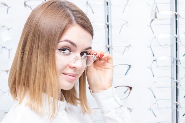 Cuidados de saúde, pessoas, visão e conceito de visão. menina sorrindo experimentando óculos na loja.