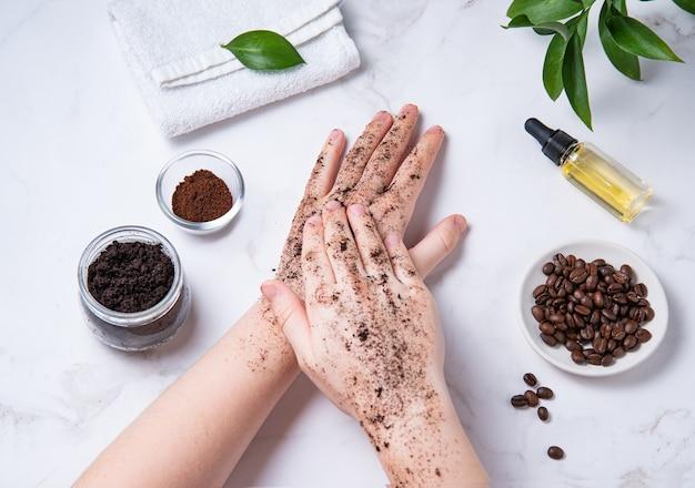 Cuidados de spa em casa para a pele das mãos e das unhas. uma jovem faz uma massagem nas mãos com uma esfoliação caseira de café com azeite de oliva sobre fundo de mármore. vista do topo