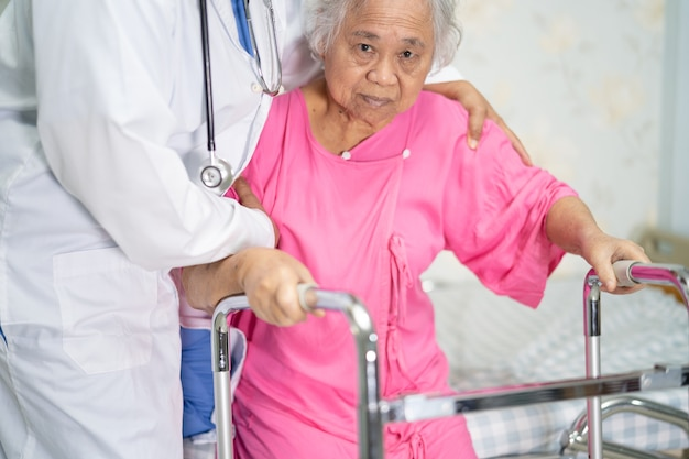 Cuidados médicos asiáticos ajudam e apoiam a caminhada de paciente idosa com andador