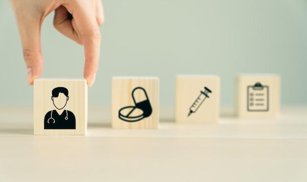 Cuidados médicos do ícone e médicos no bloco de madeira que empilha na tabela, conceito do seguro de saúde.