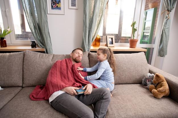 Cuidadosa filhinha fofa colocando um suéter de lã quente no pai tirando uma soneca no sofá depois de ler o livro de histórias