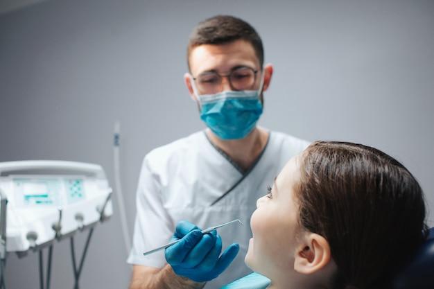 Cuidadoso dentista masculino segurar ferramenta na mão. ele olha para a garota sentada na cadeira odontológica no quarto. ela mantém a boca aberta.