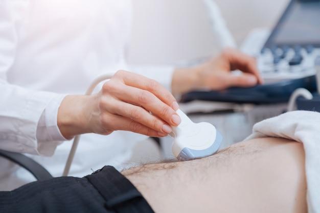 Cuidadoso envolveu um médico diligente trabalhando na clínica, ao mesmo tempo em que realizava varredura ultrassônica do abdômen e usava transdutor linear de ultrassom e máquina de ultrassom
