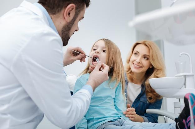 Cuidamos de nossos dentes juntos. mãe carinhosa e amorosa, certificando-se de que os dentes de seu filho sejam saudáveis, visitando o médico regularmente