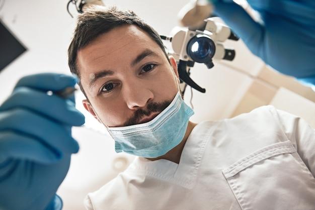 Cuidando de você, seu sorriso, jovem dentista do sexo masculino olha para os dentes com a boca aberta do paciente