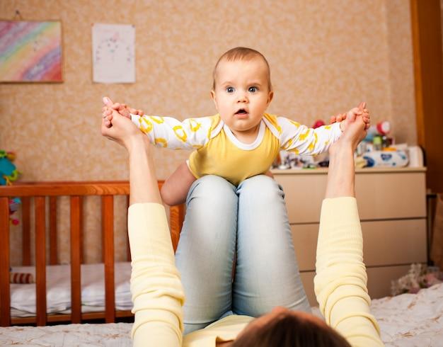 Cuidar de uma jovem mãe não identificada em roupas casuais brinca de avião com sua encantadora filha bonita de meio ano de idade na cama no quarto das crianças.
