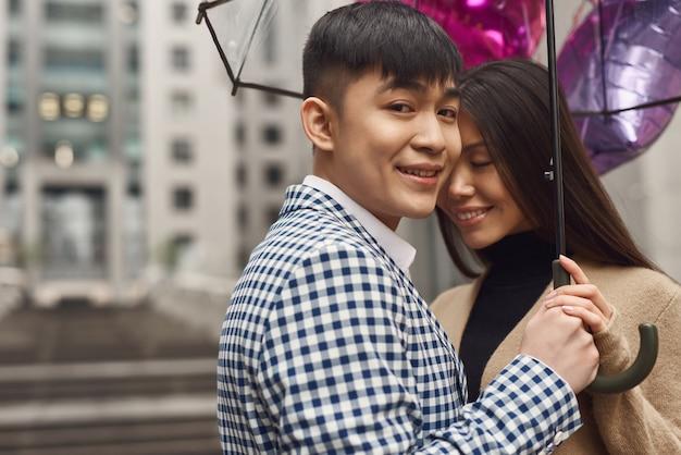 Cuide da mulher amada casal sob o guarda-chuva.