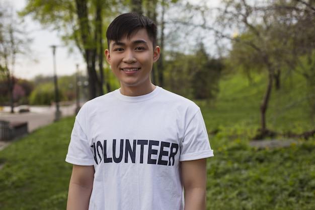 Cuide da natureza. voluntário atraente do sexo masculino posando ao ar livre e sorrindo para a câmera