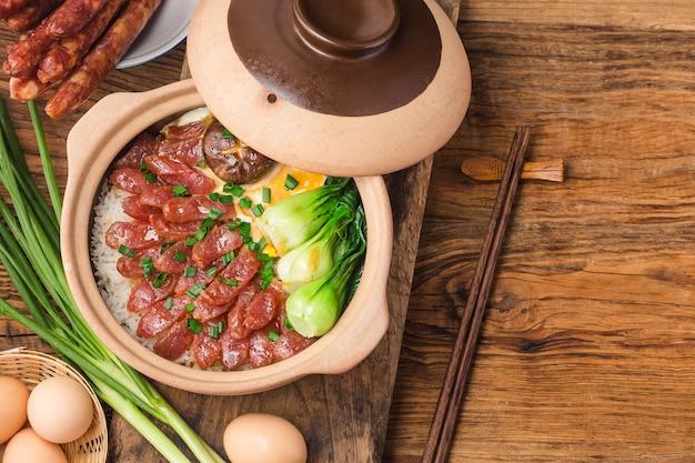 Culinária cantonesa de arroz claypot com carnes enceradas