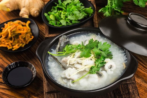Culinária chinesa congee com rodelas de peixe na caçarola
