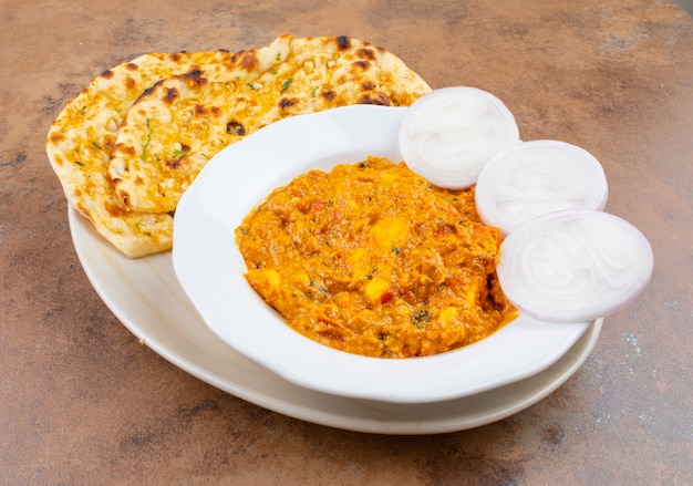 Culinária indiana paneer doce e picante pasanda servido com alho nan