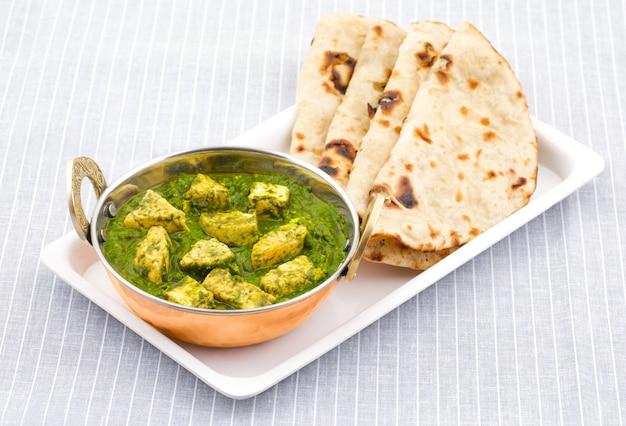 Culinária indiana saudável palak paneer servido com roti tandoori