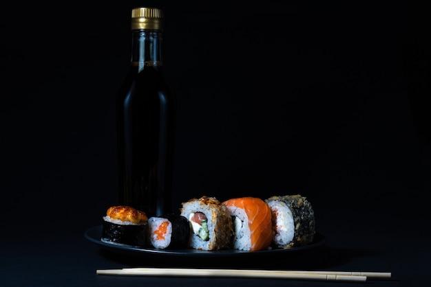 Culinária japonesa sushi maki e nigiri em um fundo preto, molho de soja e palitos de madeira