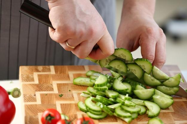Culinária masculina cortando pepino verde para dieta