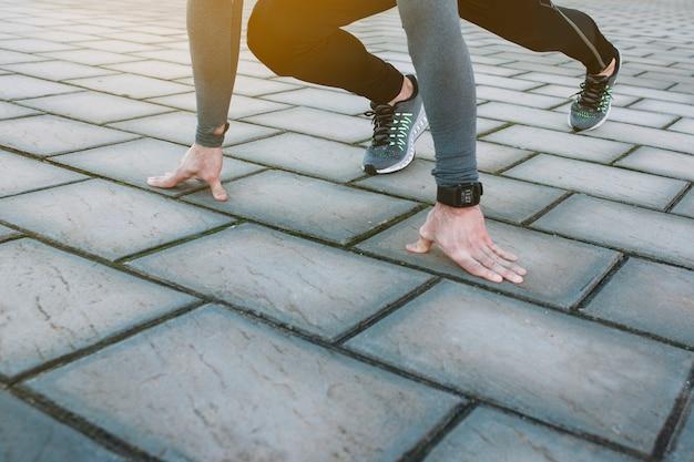 Cultivar esportista em posição de agachamento começar