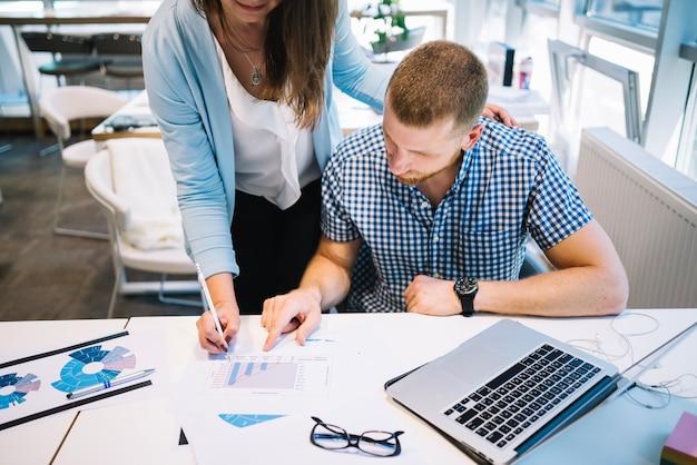 Cultivar mulher ajudando homem com gráficos