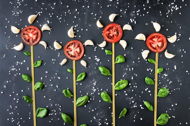Cultivo de flores feitas de macarrão, tomate e manjericão em um escuro