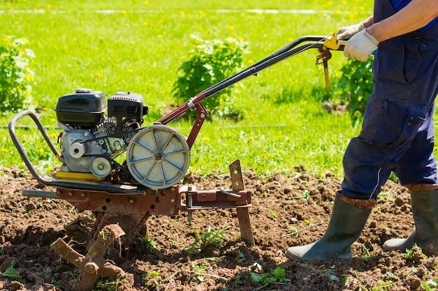 Cultivo de um jardim por um motocultivador. arando a terra. afrouxando antes de pousar. agricultura e agricultura.