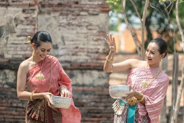 Cultura da tailândia. meninas tailandesas e mulheres tailandesas que jogam espirrando a água durante com o traje tradicional tailandês no templo do festival de songkran do festival de ayutthaya tailândia.