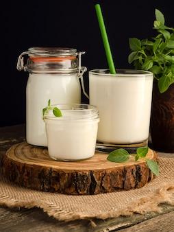 Cultura inicial de laticínios para a preparação de produtos lácteos fermentados, iogurte, kefir, leite fermentado cozido em um copo sobre um corte de madeira