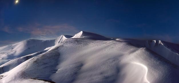 Cume da montanha coberto de neve à noite na lua e primeiro amanhecer raios pastel iluminação, ucrânia, montanhas dos cárpatos, svydovets range, blyznytsja mount.