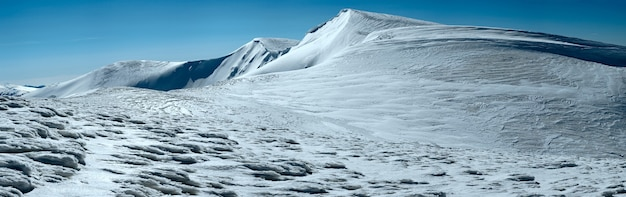 Cume de montanhas de inverno com picos de neve salientes e trilhas de snowboard no fundo do céu azul (ucrânia, mt dos cárpatos, cordilheira svydovets, monte blyznycja, estação de esqui drahobrat).