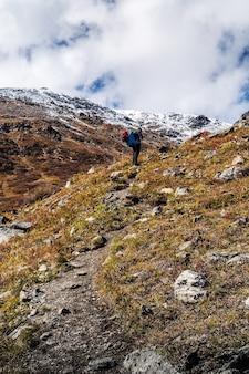 Cume severo-chuy, passagem uchitel, república de altai, rússia - 16 de setembro de 2019: um turista em um caminho sobe colina acima