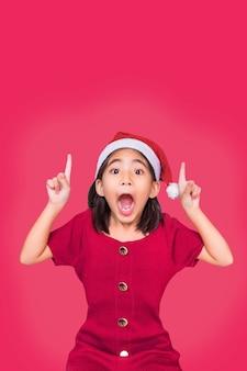 Cumprimentando a menina santa, apontar para cima para copiar o espaço no topo da parede vermelha isolada para o natal