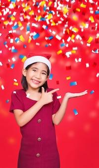 Cumprimentando santa menina aponte para recomendar um produto disponível para o natal