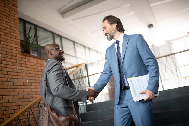 Cumprimentando-se. dois colegas sorrindo enquanto apertam as mãos durante uma reunião pela manhã