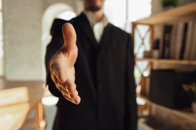 Cumprimentar alguém. feche de mãos masculinas brancas. conceito de negócio, finanças, trabalho, compras ou vendas online.