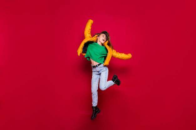 Cumprimento da garota feliz e animada pulando de jaqueta amarela e suéter verde no vermelho