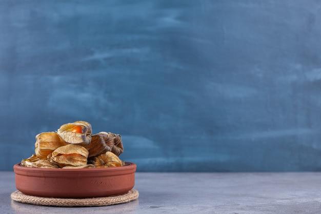 Cumquats secos saudáveis colocados em uma placa de argila.
