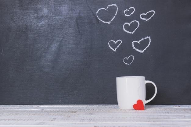 Cup com um quadro-negro atrás com corações desenhados