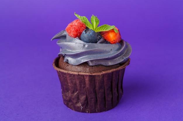 Cupcake bonito contra roxo escuro saturado